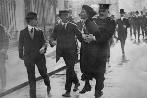 Emmeline Pankhurst sendo presa enquanto tentava apresentar uma petição ao rei no Palácio de Buckingham, em 21 de maio de 1914.