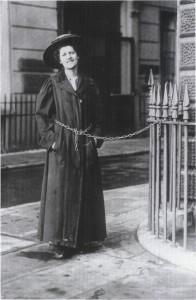 Suffragette acorrentada em grade, protestando pelo voto.